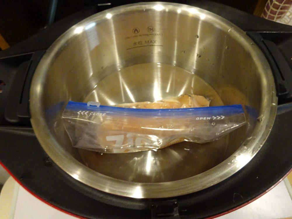 ホットクックの鍋に水を入れ鶏むね肉が入った袋を沈めます